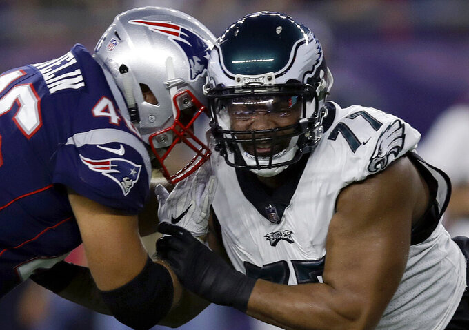 FILE- In this Aug. 16, 2018, file photo, Philadelphia Eagles defensive end Michael Bennett (77) tries to move past a block from New England Patriots fullback James Develin (46) during the first half of a preseason NFL football game in Foxborough, Mass. Develin is one of the few remaining true fullbacks in the NFL whose primary job is to just put his pads down and block. (AP Photo/Charles Krupa, File)