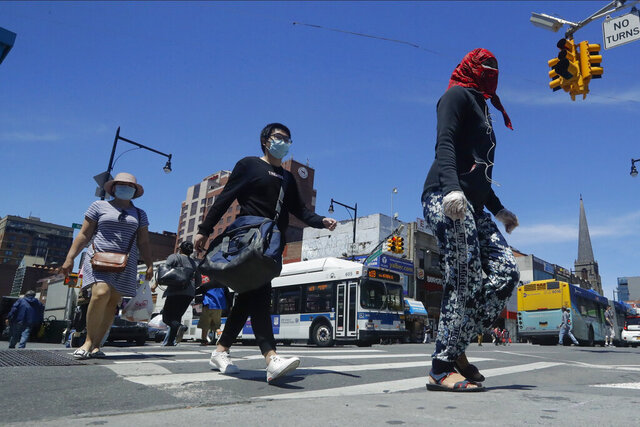 Pedestrians wear face coverings and protective masks as they cross Mains street, Monday, June 8, 2020, in the Flushing section of the Queens borough of New York. After three bleak months, New York City will try to turn a page when it begins reopening Monday after getting hit first by the coronavirus, then an outpouring of rage over racism and police brutality. (AP Photo/Frank Franklin II)