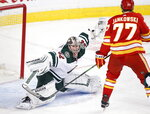 Minnesota Wild goaltender Alex Stalock (32) makes a save against Calgary Flames centre Mark Jankowski (77) during the first period of an NHL hockey game Thursday, Jan. 9, 2020, in Calgary, Alberta. (Larry MacDougal/The Canadian Press via AP)