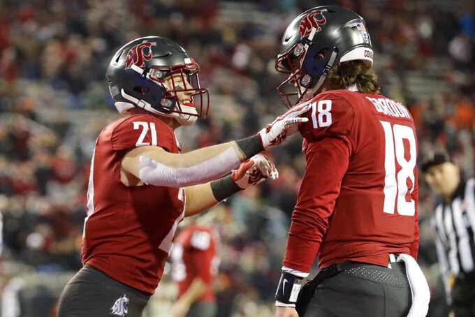 Washington State running back Max Borghi, left, celebrates with quarterback Anthony Gordon after Borghi scored a touchdown against Oregon State during the second half of an NCAA college football game, Saturday, Nov. 23, 2019, in Pullman, Wash. Washington State won 54-53. (AP Photo/Ted S. Warren)