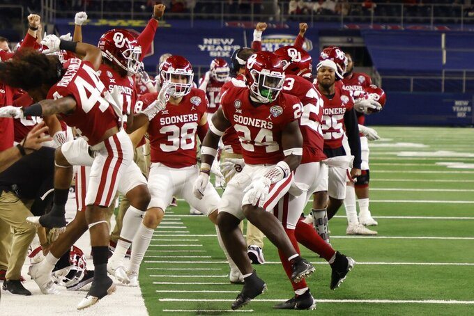 Oklahoma team members on the sideline celebrate with linebacker Brian Asamoah (24) after Asamoah tackled Florida wide receiver Rick Wells short of the end zone on a fourth-down play in the second half of the Cotton Bowl NCAA college football game in Arlington, Texas, Wednesday, Dec. 30, 2020. (AP Photo/Michael Ainsworth)