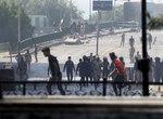 Iraqi riot police fire tear gas to disperse anti-government protesters gathering on bridge in central Baghdad, Iraq, Saturday, Nov. 9, 2019. (AP Photo/Hadi Mizban)