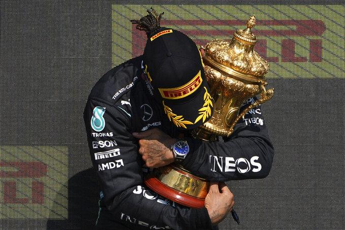 El piloto británico Lewis Hamilton, de Mercedes, celebra en el podio después de ganar en Gran Premio Británico de la Fórmula Uno, en el circuito de Silverstone, Inglaterra, el domingo 18 de julio de 2021. (AP Foto/Jon Super)