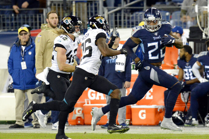Tennessee Titans running back Derrick Henry (22) runs past Jacksonville Jaguars safety Jarrod Wilson (26) and safety Andrew Wingard (42) as Henry scores a touchdown on a 74-yard run in the second half of an NFL football game Sunday, Nov. 24, 2019, in Nashville, Tenn. (AP Photo/Mark Zaleski)