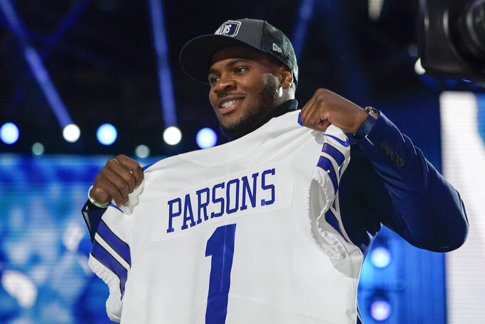 Penn State linebacker Micah Parsons holds a team jersey after the was chosen by the Dallas Cowboys with the 12th pick in the NFL football draft Thursday, April 29, 2021, in Cleveland. (AP Photo/Tony Dejak)