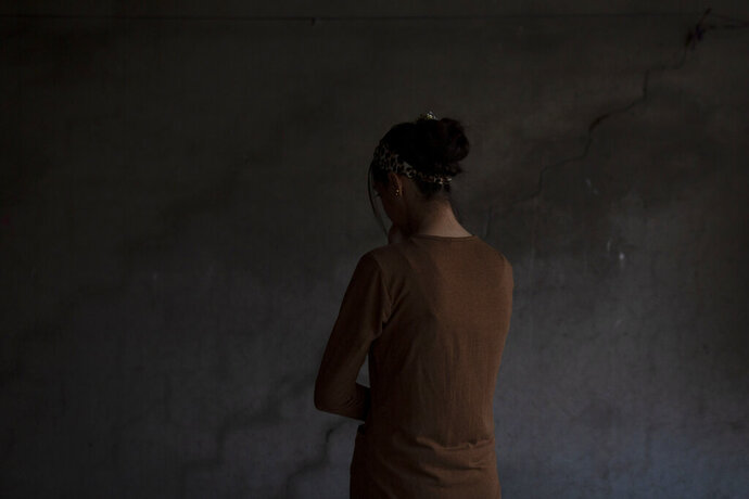 In this Nov. 14, 2019 photo, a Yazidi woman who endured five years of captivity by Islamic State militants poses for a portrait in her home in northern Iraq.
