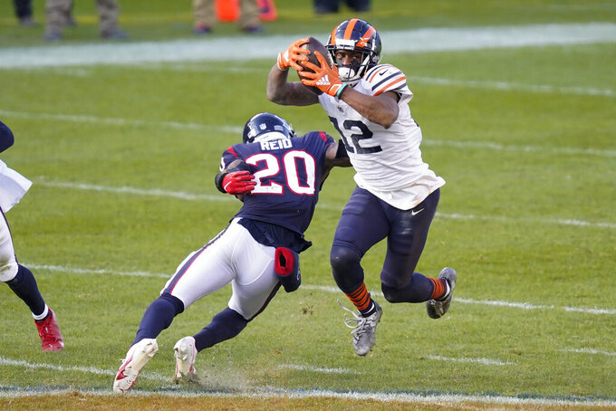 Chicago Bears' Allen Robinson (12) avoids the tackle of Houston Texans' Justin Reid (20) during the second half of an NFL football game, Sunday, Dec. 13, 2020, in Chicago. (AP Photo/Charles Rex Arbogast)