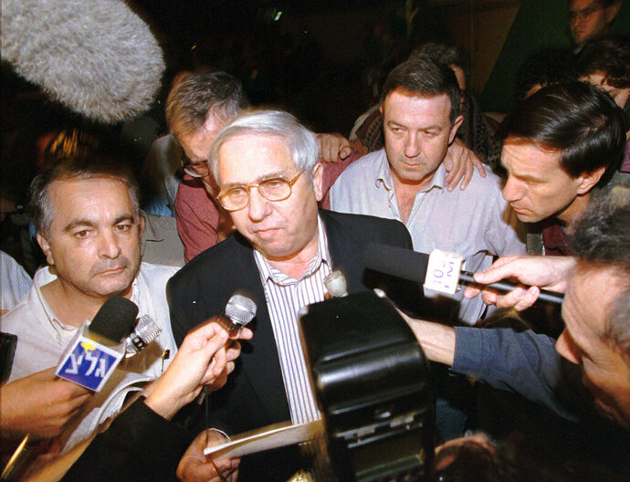 FILE - In this Nov. 4, 1995, file, photo, Eitan Haber, center, announces outside the death of Israeli Prime Minister Yitzhak Rabin, who was gunned down by a Jewish extremist following a rally in Tel Aviv. Haber, a former journalist and adviser to Rabin,  died on Wednesday, Oct. 7, 2020. He was 80. (AP Photo/Eyal Warshavsky, File)