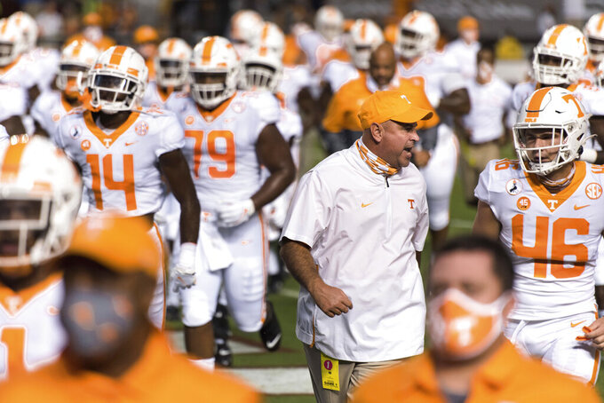 Tennessee coach Jeremy Pruitt talks with Will Albright (46) before the team's NCAA college football game against South Carolina on Saturday, Sept. 26, 2020, in Columbia, S.C. (AP Photo/Sean Rayford)