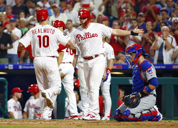 Philadelphia Phillies' J.T. Realmuto, left, celebrates his grand slam with Rhys Hoskins, center, as Chicago Cubs catcher Victor Caratini, right, looks down during the third inning of a baseball game Wednesday, Aug. 14, 2019, in Philadelphia. (AP Photo/Chris Szagola)