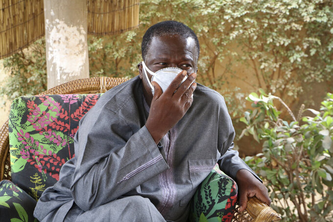 In this photo taken Tuesday, March 24, 2020, Amado Compaore sits outside his house days after his wife Rose Marie Compaore died from the new coronavirus, in Ouagadougou, Burkina Faso. Burkina Faso is one of Africa's nations hardest hit by the coronavirus with one of the highest number of fatalities in sub-Saharan Africa. (AP Photo/Sam Mednick)