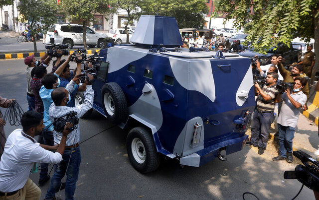 Video journalists film an armored vehicle carrying Abid Malhi, a key assailant suspected in the gang rape of a woman on a desolate highway, following his court appearance in Lahore, Pakistan, Tuesday, Oct. 13, 2020. Police arrested a key suspect in a brutal rape of a woman whose car broke down on a deserted highway major highway near the eastern city of Lahore last month. (AP Photo/K.M. Chaudary)
