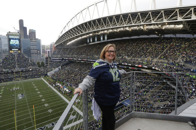 Seattle Seahawks owner Jody Allen stands on a balcony at CenturyLink Field after she raised the 12th man flag before the team's NFL football game against the Los Angeles Rams, Thursday, Oct. 3, 2019, in Seattle. (AP Photo/Stephen Brashear)