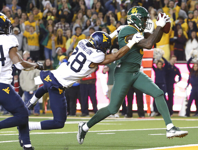 Baylor wide receiver Denzel Mims (5) catches a pass for a touchdown next to West Virginia cornerback Keith Washington Jr. (28) during the second half of an NCAA college football game in Waco, Texas, Thursday, Oct. 31, 2019. (AP Photo/Jerry Larson)