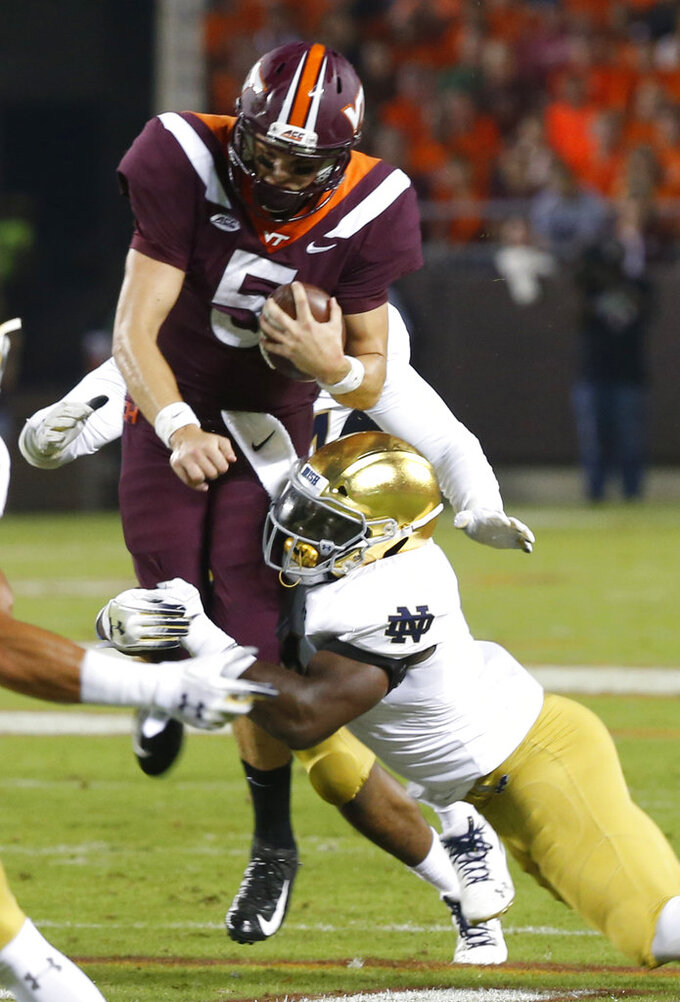 Virginia Tech quarterback Ryan Willis (5) is tackled by Notre Dame linebacker Te'von Coney during the first half of an NCAA college football game in Blacksburg, Va., Saturday, Oct. 6, 2018. (AP Photo/Steve Helber)