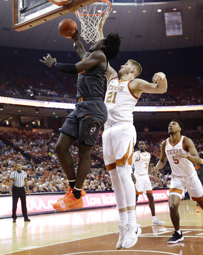 Oklahoma State guard Isaac Likekele, left, drives to the basket past Texas forward Dylan Osetkowski (21) during the first half of an NCAA college basketball game, Saturday, Feb. 16, 2019, in Austin, Texas. (AP Photo/Eric Gay)