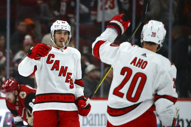 Carolina Hurricanes center Sebastian Aho (20) celebrates his empty-net goal against the Arizona Coyotes with defenseman Trevor van Riemsdyk (57) during the third period of an NHL hockey game Thursday, Feb. 6, 2020, in Glendale, Ariz. The Hurricanes won 5-3. (AP Photo/Ross D. Franklin)