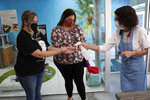 Celyta Jackson, owner of the Cat Cafe South Beach, right, offers hand sanitizer to customers Jacquelin Johnson, left, and Ruthie Menendez, center, during the coronavirus pandemic, Wednesday, July 29, 2020, in Miami Beach, Fla.The cafe offers a place for cat lovers to spend time with cats, which are also available for adoption. Jackson will be closing her business at the end of the week as the tourism sector in Miami-Dade County is suffering due to the pandemic. (AP Photo/Lynne Sladky)