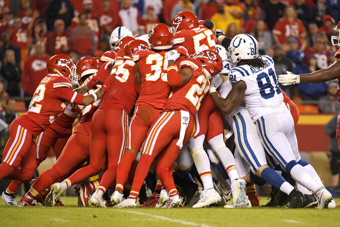A scrum of Kansas City Chiefs players, left, struggles to stop an Indianapolis Colts carrier during the second half of an NFL football game in Kansas City, Mo., Sunday, Oct. 6, 2019. (AP Photo/Reed Hoffmann)
