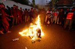 Supporters of Jamaat-e-Islami, a religious political party, burn an effigy of French President Emmanuel Macron during a protest against Macron and the republishing of caricatures of the Prophet Muhammad they deem blasphemous, close to French consulate in Karachi, Pakistan, Wednesday, Oct. 28, 2020. Muslims have been calling for both protests and a boycott of French goods in response to France's stance on caricatures of Islam's most revered prophet. (AP Photo/Fareed Khan)