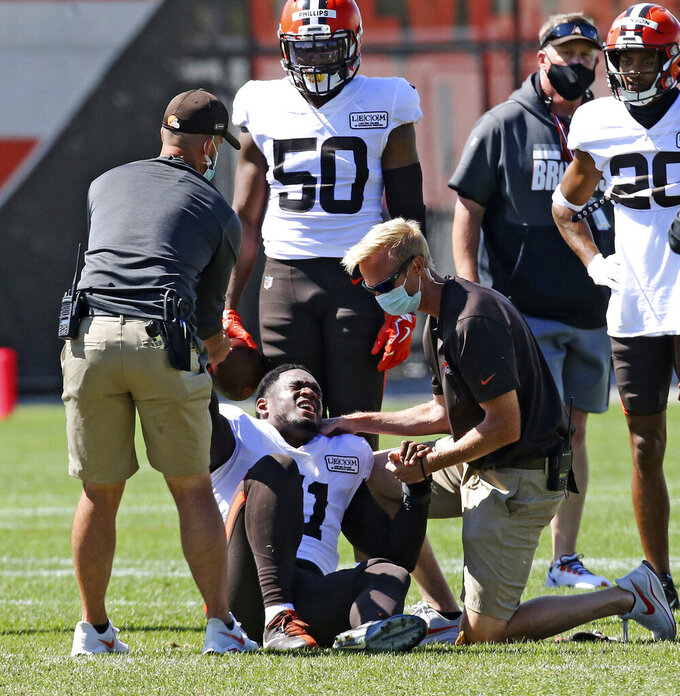 Cleveland Browns linebacker Mack Wilson is helped up by the team's medical staff after suffering a knee injury in a 7-on-7 drill during training camp, Tuesday, Aug. 18, 2020, in Berea, Ohio. (John Kuntz/The Plain Dealer via AP)