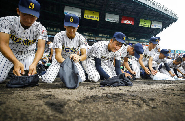 Akashi Commercial High School baseball players collect dirt of the grounds after being defeated by Riseisha High School during a semifinal game at the National High School Baseball Championship at Koshien Stadium in Nishinomiya, western Japan, on Aug. 20, 2019. Every year, after a team loses, the players, many weeping uncontrollably, scrape the dirt from foul territory near the dugout to take home as a memento. Japanese high school baseball players who had their heart set on going to the annual tournament won't be able to go, with the 2020 event canceled over the coronavirus pandemic. (Kyodo News via AP)