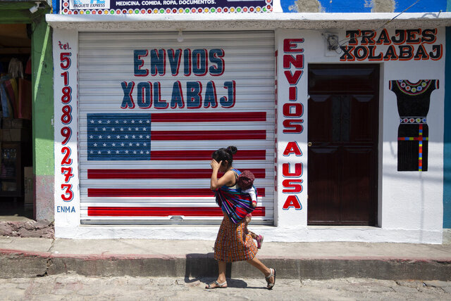 In this April 3, 2020 photo, a woman carrying a child walks past a closed courier business featuring a U.S. flag and the Spanish phrase:
