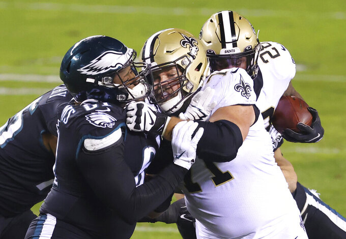 FILE - Philadelphia Eagles' Raequan Williams, left foreground, battles New Orleans Saints' Ryan Ramczyk, center, during an NFL football game in Philadelphia, in this Sunday, Dec. 13, 2020, file photo. Saints right tackle Ryan Ramczyk has agreed to a five-year extension worth up to $96 million, a person with knowledge of the situation said. The person spoke to The Associated Press on Wednesday, June 30, 2021, because the new contract for the 2019 All-Pro offensive lineman has not been announced. (AP Photo/Rich Schultz)