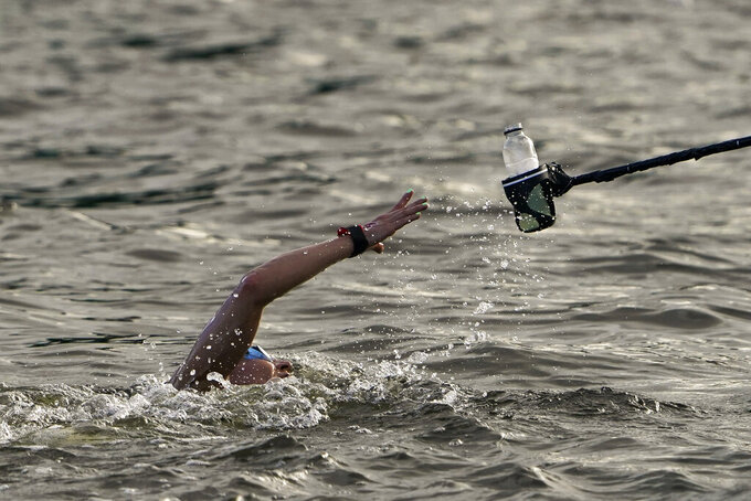 Souad Nefissa Cherouati, of Algeria, grabs a drink at a feeding station during the women's marathon swimming at the 2020 Summer Olympics, Wednesday, Aug. 4, 2021, in Tokyo, Japan. (AP Photo/Jae C. Hong)