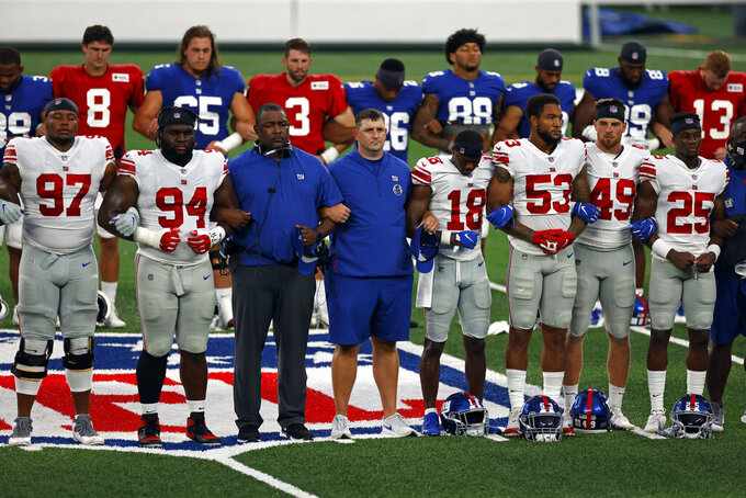 FILE - New York Giants head coach Joe Judge, center, stands with arms linked with his players to make a social injustice statement prior to their scrimmage at the NFL football team's training camp in East Rutherford, N.J., Friday, Aug. 28, 2020. The Giants will kick off the Joe Judge era against the Pittsburgh Steelers on Monday night, Sept. 14. (AP Photo/Adam Hunge, File)