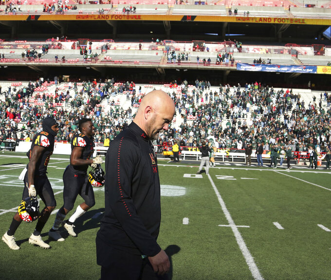 FILE - In this Saturday, Nov. 3, 2018, file photo, Maryland interim head coach Matt Canada walks off the field with his squad after losing 24-3 to Michigan State in an NCAA college football game in College Park, Md. Canada faces an uncertain future, despite keeping the football team together and forging a winning record amid the chaos surrounding the program.(AP Photo/Gary Cameron, File)