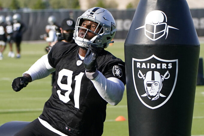 Las Vegas Raiders defensive end Yannick Ngakoue takes part in a drill during an NFL football practice Tuesday, June 15, 2021, in Henderson, Nev. (AP Photo/John Locher)