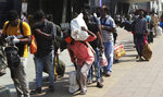 People wearing masks as a precaution against the coronavirus walk to board trains at Lokmanya Tilak Terminus in Mumbai, India, Friday, April 16, 2021. Migrant workers are swarming rail stations in India's financial capital Mumbai to go to their home villages as virus-control measures dry up work in the hard-hit region. The government of Maharashtra state imposed lockdown-like curbs on Wednesday for 15 days to check the spread of the virus. It closed most industries, businesses and public places and limited the movement of people, but didn't stop the bus, train and air services. An exodus ensued, with panicked day laborers hauling backpacks onto overcrowded trains leaving Mumbai, travel that raises fears of infections spreading in rural areas. (AP Photo/Rajanish Kakade)