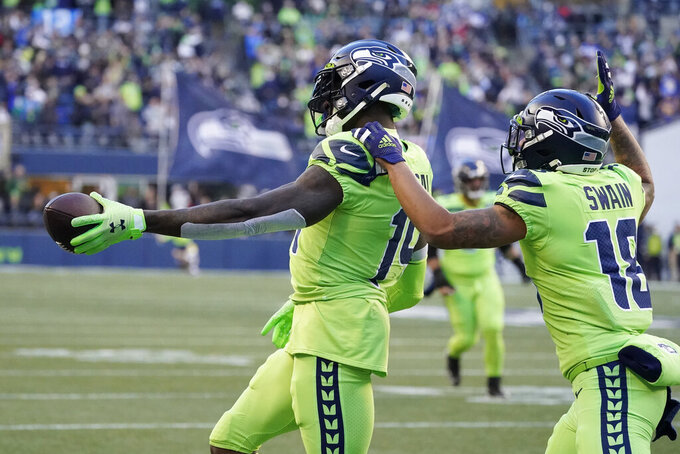 Seattle Seahawks wide receiver DK Metcalf (14) celebrates with Freddie Swain after Metcalf scored a touchdown against the Los Angeles Rams during the first half of an NFL football game, Thursday, Oct. 7, 2021, in Seattle. (AP Photo/Elaine Thompson)