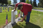 Frank Groblebe places lilacs at the grave of his parents, Frank and Helen Groblebe, at the Mountview Cemetery in Billings, Mont., Monday, May 25, 2020. No new cases of the coronavirus were reported in Montana on Monday for the fifth straight day. (AP Photo/Matthew Brown)