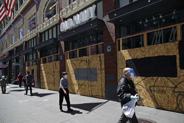 Masked people walk past a boarded up Old Navy clothing store on Wednesday, May 27, 2020, in San Francisco. While much of California moves swiftly to reopen things like hair salons under Gov. Gavin Newsom's guidance, the San Francisco Bay Area is continuing to keep the brakes on. Some health officials are questioning whether the state is taking enough time to assess the effects of reopening things like stores before jumping ahead to broader re-openings, risking a surge in infections. (AP Photo/Ben Margot)