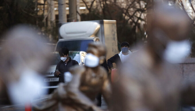 Pedestrians wearing face masks as a precaution against the coronavirus, walk near the statues with masks in Incheon, South Korea, Sunday, Feb. 7, 2021. (AP Photo/Lee Jin-man)