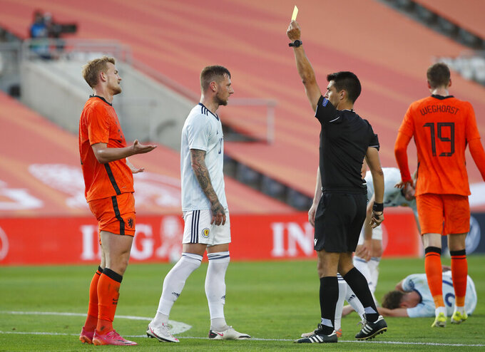 Netherlands' Matthijs de Ligt, left, is shown a yellow card by the referee during the international friendly soccer match between the Netherlands and Scotland at the Algarve stadium outside Faro, Portugal, Wednesday June 2, 2021. (AP Photo/Miguel Morenatti)