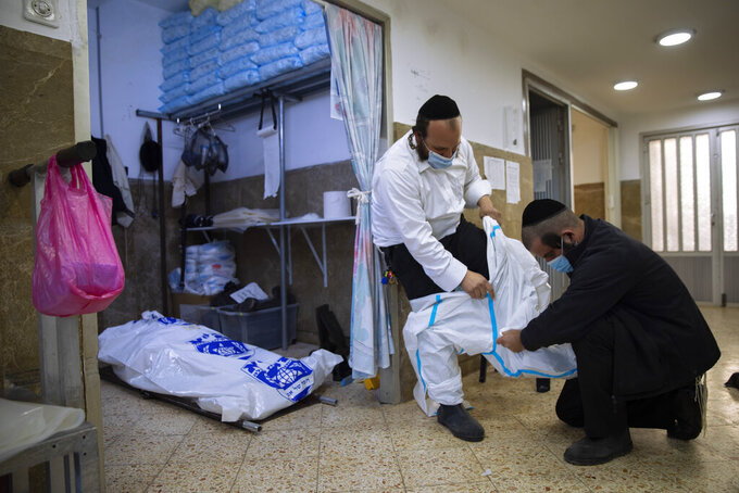 """Workers from """"Hevra Kadisha,"""" Israel's official Jewish burial society, get dressed in full protective gear to prepare a body for a funeral procession, at a special morgue for people who died from COVID-19, during a nationwide lockdown to curb the spread of the coronavirus, in Jerusalem, Tuesday, Feb. 2, 2021. (AP Photo/Oded Balilty)"""