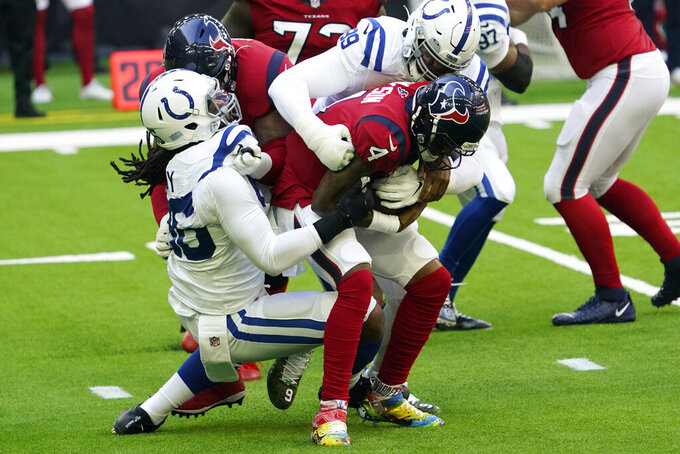 Houston Texans quarterback Deshaun Watson (4) is sacked by Indianapolis Colts defensive tackle DeForest Buckner (99) and defensive end Denico Autry (96) during the first half of an NFL football game Sunday, Dec. 6, 2020, in Houston. (AP Photo/David J. Phillip)