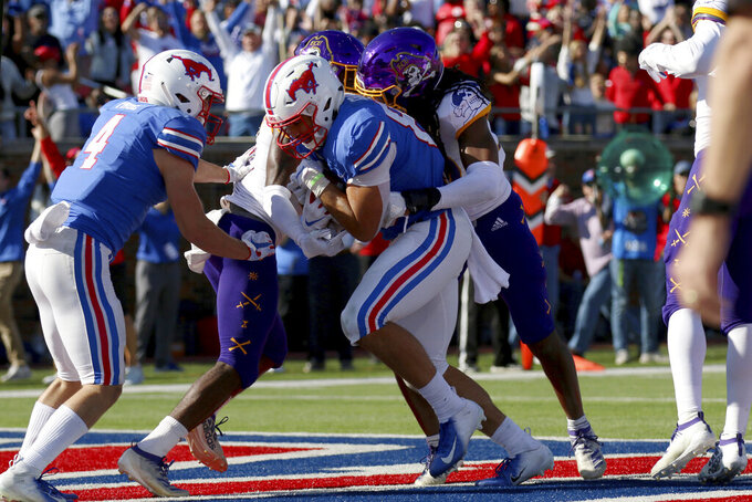 SMU tight end Kylen Granson, center, scores a touchdown while wide receiver Tyler Page (4) looks on during the second half of an NCAA college football game, Saturday, Nov. 9, 2019, in Dallas. (AP Photo/Roger Steinman)