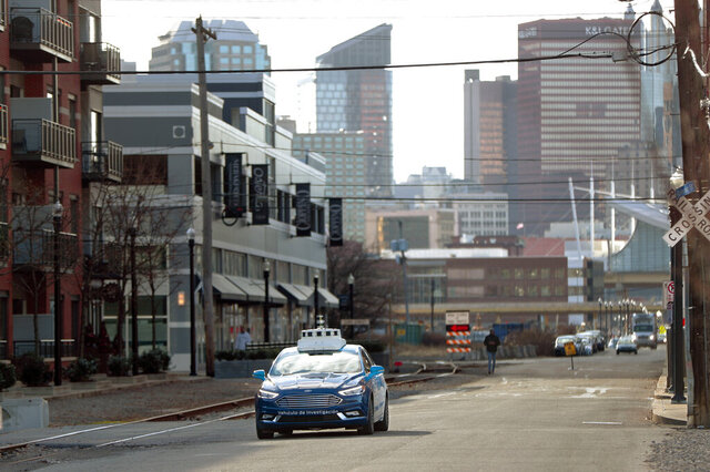 FILE - In this Dec. 18, 2018 file photo, one of the test vehicles from Argo AI, Ford's autonomous vehicle unit, navigates through the strip district near the company offices in Pittsburgh. The nation's road-safety regulator is under fire again for what critics call lax oversight of tests involving autonomous vehicles. The nation's top transportation safety investigator said Tuesday, Nov. 19, 2019, that the National Highway Traffic Safety Administration doesn't give enough direction to companies developing more automated cars. (AP Photo/Keith Srakocic, File)