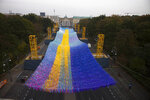 The skynet artwork 'Visions In Motion', overhangs the 'Strasse des 17. Juni' (Street of June 17) boulevard in front of the Brandenburg Gate in Berlin, Germany, Friday, Nov. 1, 2019. The art work by Patrick Shearn was made with about 100.000 streamers with written messages and is part of the celebrations marking the 30th anniversary of the fall of the Berlin Wall on Nov 9, 2019. (AP Photo/Markus Schreiber)