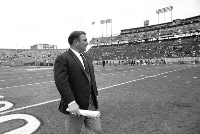 FILE - In this Jan. 11, 1970 file photo, Kansas City Chiefs coach Hank Stram walks on the field prior to the Super Bowl game with the Minnesota Vikings in New Orleans.   As the Chiefs prepare to play the San Francisco 49ers on Sunday, Feb. 2, 2020, many members of the 1970 team never lived to see the the Chiefs return to the championship game, and many others are in failing health.    (AP Photo)