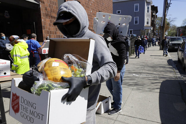 A person wearing mask and gloves out of concern for the coronavirus carries a box of donated food away from a Salvation Army food pantry, Tuesday, May 5, 2020, in Chelsea, Mass. (AP Photo/Steven Senne)