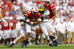 CORRECTS SCORE TO 35-14- Michigan defensive lineman Aidan Hutchinson, left, and defensive back Josh Metellus, right, tackle Wisconsin running back Jonathan Taylor, center, during the second half of an NCAA college football game Saturday, Sept. 21, 2019, in Madison, Wis. Wisconsin won 35-14. (AP Photo/Andy Manis)