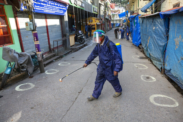 A government health worker sprays sanitiser on a street shut down to prevent the spread of the coronavirus in Dharmsala, India, Thursday, Dec. 10, 2020. (AP Photo/Ashwini Bhatia)