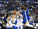 Dallas Mavericks forward Luka Doncic (77) looks to shoot as Golden State Warriors forward Draymond Green defends in the first half of an NBA basketball game Saturday, March 23, 2019, in Oakland, Calif. (AP Photo/John Hefti)