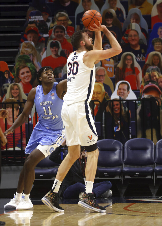 Virginia forward Jay Huff (30) shoots next to North Carolina forward Day'Ron Sharpe (11) during an NCAA college basketball game Saturday, Feb. 13, 2021, in Charlottesville, Va. (Andrew Shurtleff/The Daily Progress via AP, Pool)