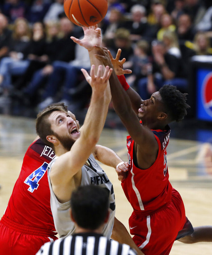 Colorado forward Lucas Siewert, front, pulls in a rebound as Arizona Wildcats center Chase Jeter, back left, and guard Brandon Randolph defend in the second half of an NCAA college basketball game Sunday, Feb. 17, 2019, in Boulder, Colo. Colorado won 67-60. (AP Photo/David Zalubowski)